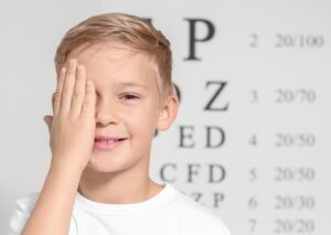 Young boy covering one eye with an eye chart in the background
